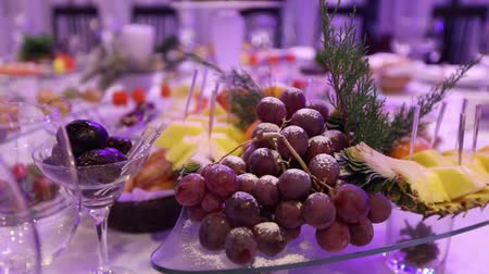 elegant dessert : Fruit and food on the banquet table in the restaurant, pieces of pineapple and bunches of grapes on the banquet table, decoration of the banquet hall, restaurant interior