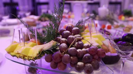 慶典 : Fruit and food on the banquet table in the restaurant, pieces of pineapple and bunches of grapes on the banquet table, decoration of the banquet hall, restaurant interior