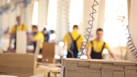 blurring : Furniture factory workers in yellow overalls collect furniture, Furniture manufacture