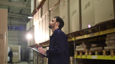 supervisor : The warehouse worker makes an inventory of the goods. The male storekeeper recounts the goods in the warehouse and makes notes. Manager work in the warehouser Stock Footage