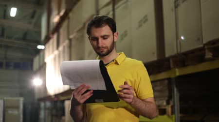 profundidade de campo rasa : The warehouse worker makes an inventory of the goods. The male storekeeper recounts the goods in the warehouse and makes notes, warehouse worker, industrial interior, a warehouse interior Stock Footage