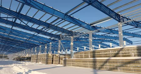 proti : Modern storehouse construction site, the structural steel structure of a new commercial building against a clear blue sky in the background, Construction of a modern factory or warehouse