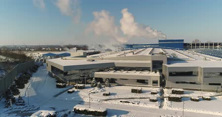área de trabalho : A modern factory or commercial building, the exterior of a modern factory or plant, building facade and car parking, panoramic view from the air, winter time, sunny day, blue sky Stock Footage