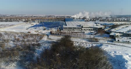 estrutural : A modern factory or commercial building, the exterior of a modern factory or plant, building facade and car parking, panoramic view from the air, winter time, sunny day, blue sky Vídeos