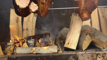 špejle : Large chunks of delicious pork hams cooked on an open fire. The street food. Food outdoors. Camping and cooking on a spit over the fire, man cooks large pieces of meat on a spit on fire, closeup
