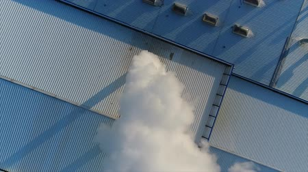 trąbka : smoke from a pipe on the roof of a factory or factory, the roof of a production room with a pipe, white thick smoke exits the pipe Wideo