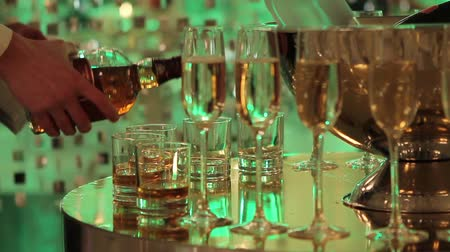 toalha de mesa : Glasses of champagne and wine on the buffet table, a bottle of champagne or wine in a bucket on a background of people dancing, blurred silhouettes of people Stock Footage