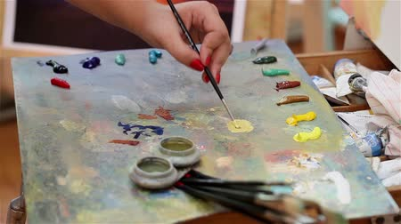 expressionism : Artist mixes paint on the palette, Art brush mixed paint on the palette, artist brush mix color oil painting on palette, artistic brush, hand close-up Stock Footage