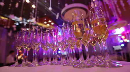 szampan : Glasses with champagne on the table in the restaurant, glasses of champagne on festive table, Clean glasses on a table prepared by the bartender for champagne and wine Wideo