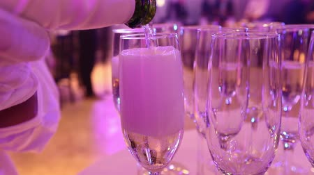 официант : The waiter pours champagne in glasses, Glasses with champagne on the table in the restaurant, glasses of champagne on festive table, Clean glasses on a table prepared by the bartender for champagne