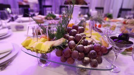 beállítás : Fruit and food on the banquet table in the restaurant, pieces of pineapple and bunches of grapes on the banquet table, decoration of the banquet hall, restaurant interior