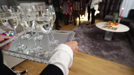 utensílio : A woman is carrying glasses with a drink on a tray, glasses with champagne or water on a silver tray