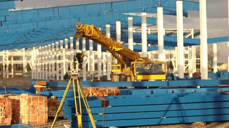 levelling : Optical Theodolite, Builders Theodolite, construction theodolite on the background of the construction of a large industrial building or warehouse, construction work