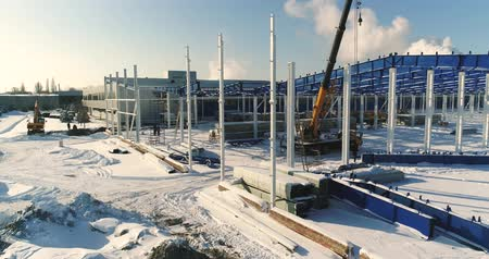 construction crane : Construction of a modern factory or plant, Industrial area in winter, panoramic view from the air. Modern plant on the snow-covered field, the structural steel structure of a new commercial building