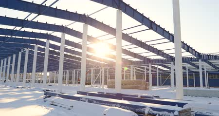 wide angle view : Construction of a modern factory or warehouse, modern industrial exterior, panoramic view, Modern storehouse construction site, the structural steel structure of a new commercial building Stock Footage