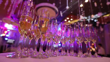 служба : Glasses with champagne on the table in the restaurant, glasses of champagne on festive table, Clean glasses on a table prepared by the bartender for champagne and wine Стоковые видеозаписи