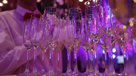 szampan : The waiter pours champagne in glasses, Glasses with champagne on the table in the restaurant, glasses of champagne on festive table, Clean glasses on a table prepared by the bartender for champagne