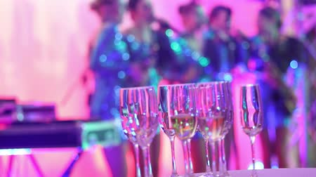 фокус : Glasses with champagne on the background of silhouettes of womens music group, a female music band performs in a restaurant or hotel lobby