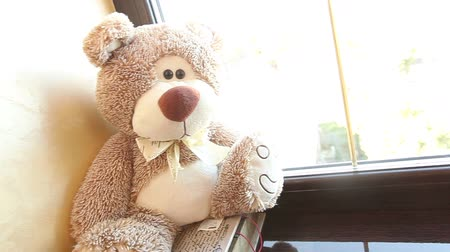 долл : Teddy bear sits on a windowsill, cute teddy bear near the window, with a butterfly on her neck, light brown, childrens soft toy, a teddy bear with a butterfly on her neck