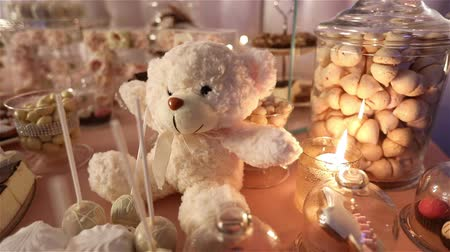 pişmiş : Candy bar in the restaurant, childrens party, birthday, a white teddy bear with a butterfly on her neck, lit candle, teddy bear on a table Candy bar, closeup