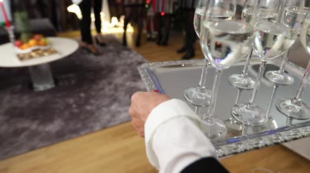 szampan : A woman is carrying glasses with a drink on a tray, glasses with champagne or water on a silver tray