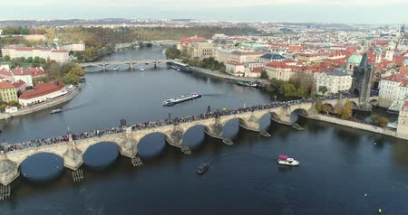 čeština : Panoramic view from above to the city of Prague and Charles Bridge, tourists on the Charles Bridge