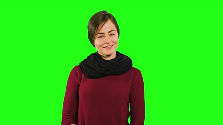 nézett le : A young modest lady smiling, squinting her eyes and looking down against a green background. Medium shot