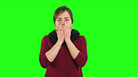 nézett le : A young lady touching her face in shock against a green background. Medium shot