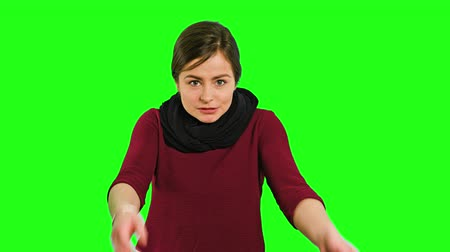 výraz : A young lady touching her face in fury and screaming against a green background. Medium shot Dostupné videozáznamy
