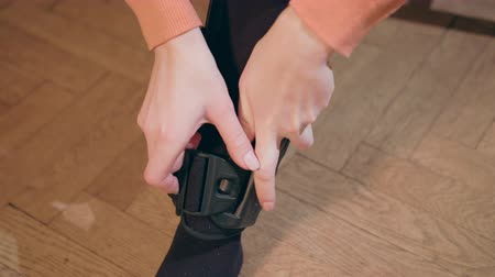 pétala : Detail of the lower half of a lady putting on a supportive leg brace. Close-up shot Stock Footage