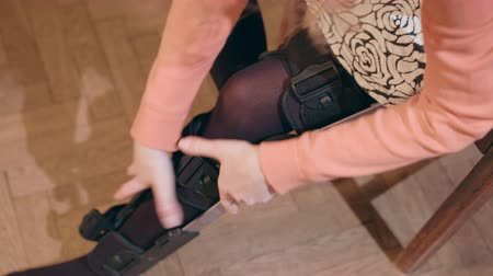 pétala : Detail of the lower half of a lady removing a supportive leg brace. Close-up shot Stock Footage