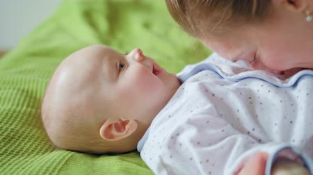 мама : Babys lying in bed on green linen and playning with its mother. Close-up shot. Soft focus