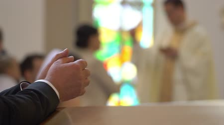 repentance : Clasped hands of man kneeling at the pew in the Church and praying. On the blurred background the catholic priest gives the holly communion to people who moving in line. Closed up. Steady. Interior. Blurred Stock Footage
