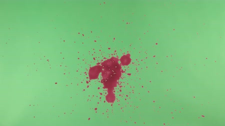 splashed : Red ink splatter over green screen background. Close-up shot Stock Footage