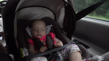 inside cars : Baby girl sleeping in child car seat. Long shot