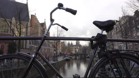 герань : Dutch bike chained to a bridge over the canals of Amsterdam. Стоковые видеозаписи