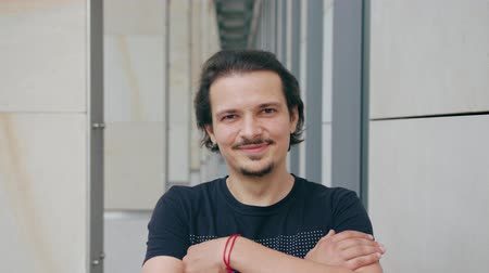 bigode : An attractive young man smiles outdoors against a modern concrete building background. Medium shot Stock Footage