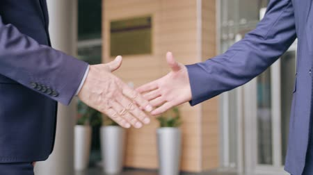 партнеры : Business people handshaking outdoors. Close-up. Soft focus Стоковые видеозаписи