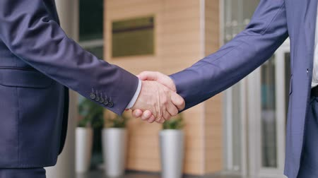 tratar : Business people handshaking outdoors. Close-up. Soft focus Vídeos