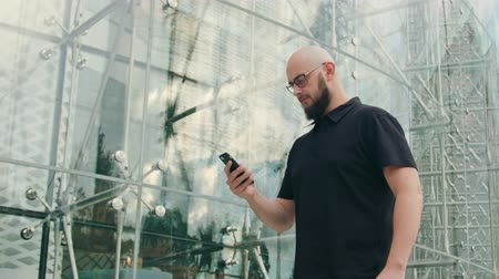 gentleman : A man with a beard wearing black glasses uses a phone in the city street. Medium shot. Soft focus