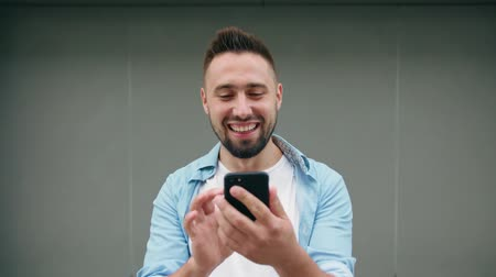 gentleman : A man with a beard smiling and using a phone against a gray background. Medium shot. Soft focus Stock Footage