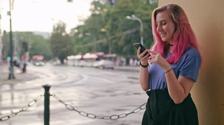 sukně : A young woman with a pink hair using a phone in the city street. Medium shot. Soft focus