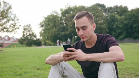 mms : A young man using a phone in the park. Medium shot. Soft focus