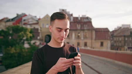 mms : A young man using a phone in the city street. Close-up shot. Soft focus Stock Footage