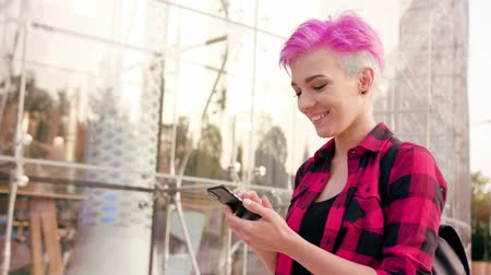 discar : A young woman with a pink short hair using a phone in the city street. Close-up shot. Soft focus. Dolly shot. Stock Footage