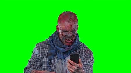 zalim : Halloween theme horrible scary zombie in clothes uses the phone isolated over green screen background