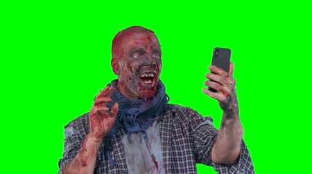 greasepaint : Man in zombie makeup makes selfie phone isolated over green screen background Stock Footage