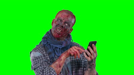lijk : Halloween theme horrible scary zombie in clothes uses the phone isolated over green screen background