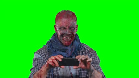zombi : Male zombie using cell phone looks and laughs standing on green background, half body shot Stok Video