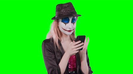 promover : Portrait of a happy cheerful blonde woman in halloween clown make-up using mobile phone isolated over green background Stock Footage